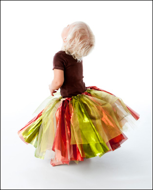 Young girl wearing a green and red tutu skirt