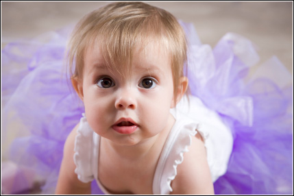 Infant wearing a purple tutu skirt