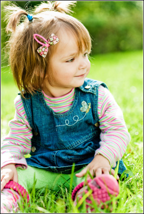 Young girl sitting in grass with hair bow